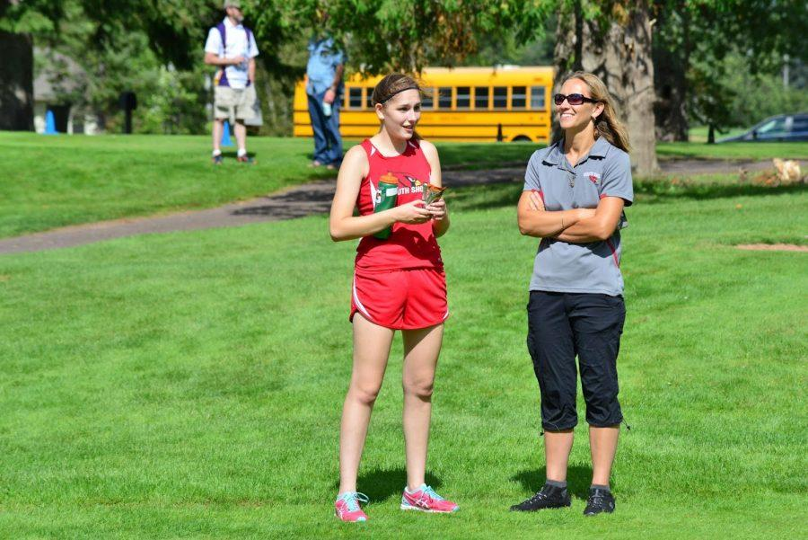 Emma Ostrenga refuels after her race with her new water bottle and protein bar while discussing details of her run with Coach Lahti.
