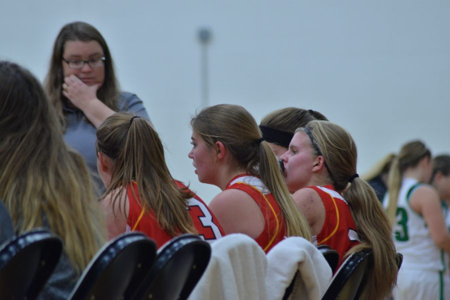 Rylee Nicoletti, Heather Ranta & Shauna Kavajecz sit on the bench for a time out while the coaches talk.