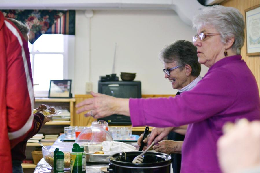 Happy to Serve!  Marilynn Finucane and Kathryn Franta of Bayfield volunteer to serve food to the boys and girls basketball teams on February 16.