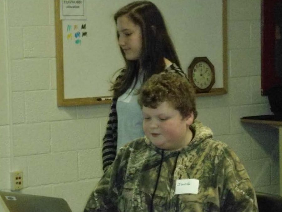 Jacob Nollet (at the computer) & Veda Dreher showcase their game, EXPERIMENT X, at the CESA12 Coding Day event.