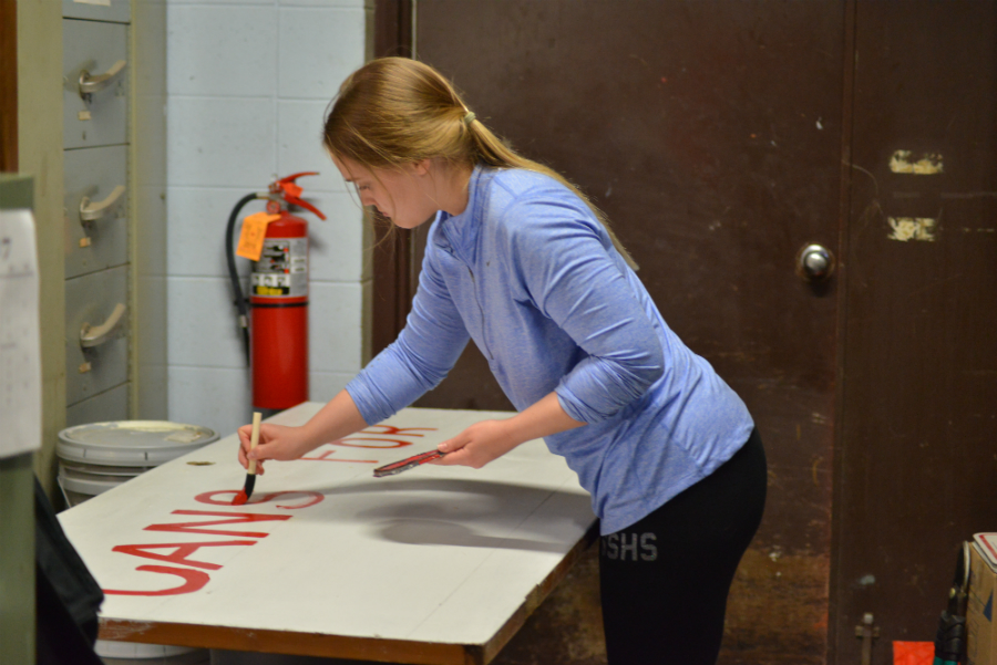 Preparing for a fundraiser, sophomore Morgan Rock paints a sign to make the can recycling bin more noticeable.