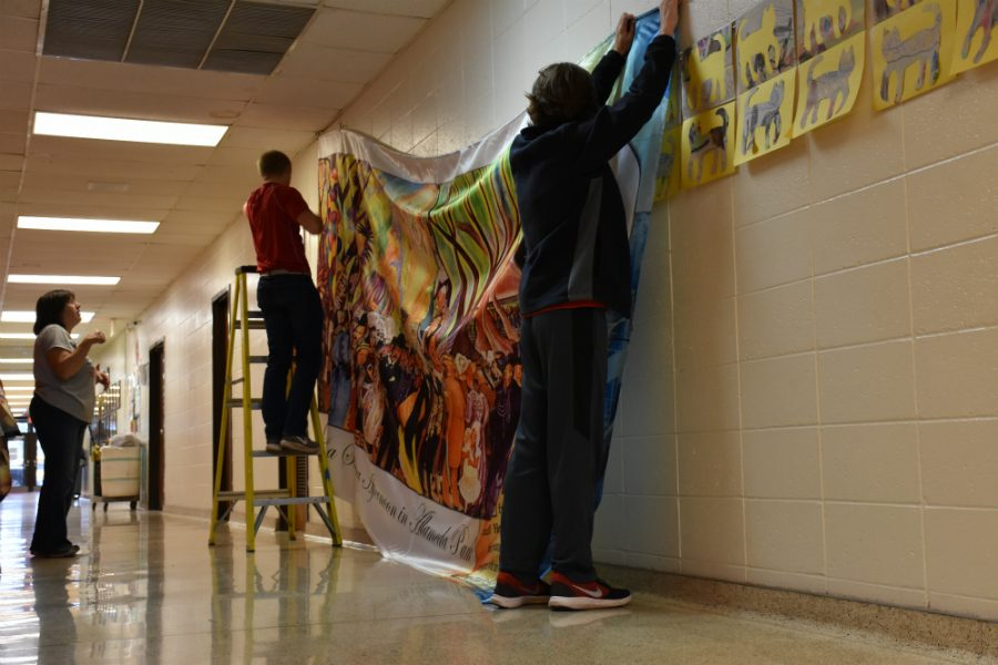 Douglas Hipsher & Dante Ray help out the janitors & Ms. Ripley with hanging the murals by the famous Diego Rivera.