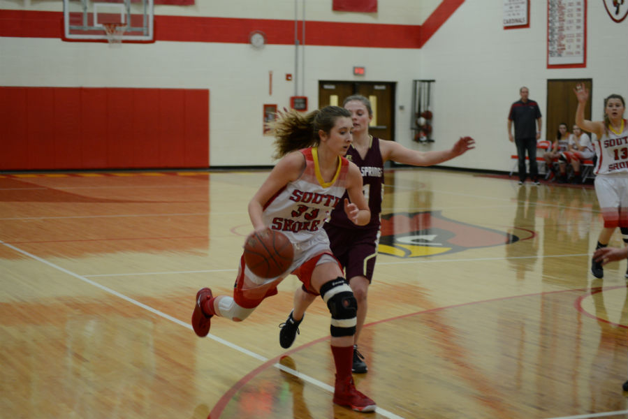 Freshman Natalie Knaack flys by a Solon Springs player during the December 15th game.