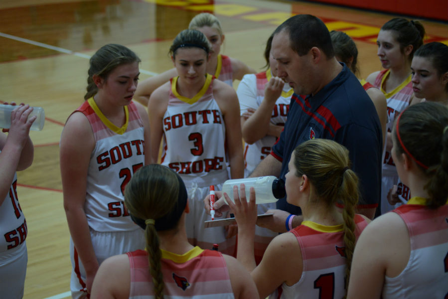 The girls huddle around Coach Tiberg as he lays the  game plan.