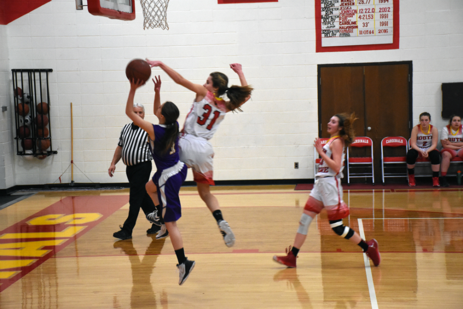 Chloe Sipsas, a freshman, denies Drummond player Jolene Yiltalo, as she attempts to make the lay-up. Natalie Knaack follows close behind, ready to get the rebound.
